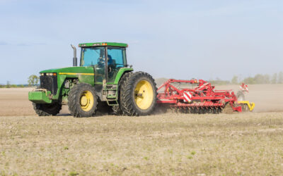 tractor with trailer plowed earth in the field
