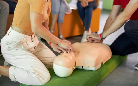 CPR class with caucasian instructors speaking and demonstrating help first aid