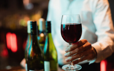 Mid section of bartender holding glass of red wine at bar counter