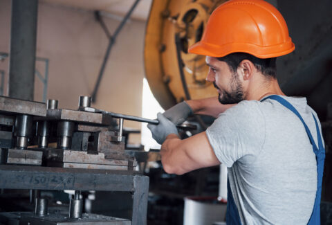 portrait-of-a-young-worker-in-a-hard-hat-at-a-large-metalworking-plant